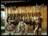 Three hunters sitting in front of a row of geese displayed on the wall behind.